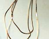 Geltono metalo trijų eilių kaklo papuošalas